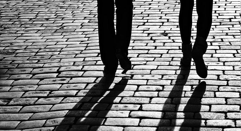 Zwei Personen werfen Schatten auf den gepflasterten Weg.