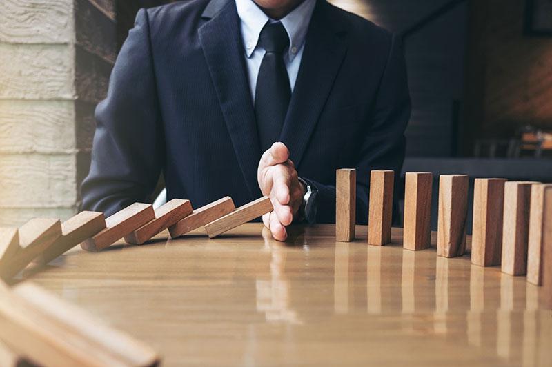 Mann im Anzug am Tisch, stoppt mit der Hand eine Reihe fallender Dominosteine