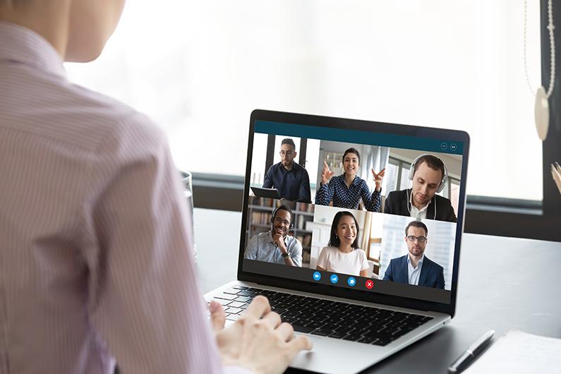 Blick von hinten über die Schulter einer Frau, die übers Laptop an einer Online-Besprechung teilnimmt
