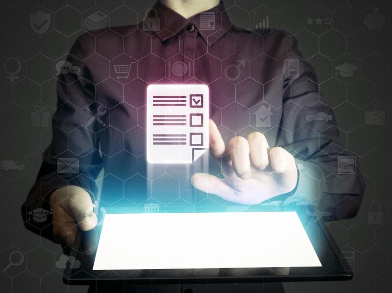 Person im schwarzen Hemd hakt mit dem Finger eine Checkliste ab, die aus einem leuchtenden Tablet aufsteigt